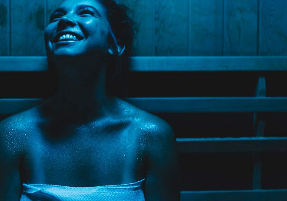 Woman in blue light therapy sauna to improve mental health