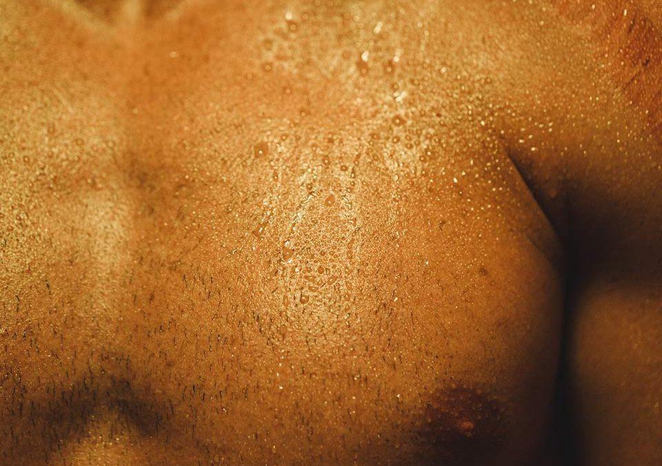 Man sweating in infrared sauna orange light